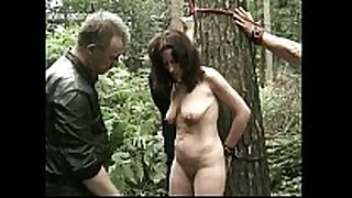Naked slave fastened to a tree got her pierced puss...